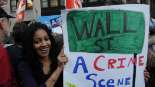 """10月5日纽约游行:一女青年举着的牌子说,""""华尔街是犯罪现场"""""""