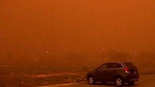 Carro estacionado em meio a nuvem de poeira vermelha em Lubbock, Texas (BBC)