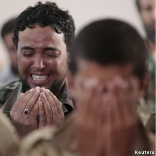 Combatente anti-Khadafi chora durante as preces de sexta-feira.