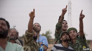 Rebeldes libios observan un avión de la OTAN.