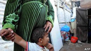 Mujer embarazada junto a uno de sus hijos