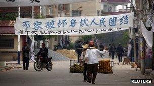 陆丰乌坎村内村民在呼吁团结的抗议横幅下走过(20/12/2011)