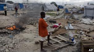 Jovem em meio a destroços de campo em Porto Príncipe, em foto de 4 de janeiro (AP)