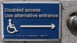 Placa sinaliza entrada para cadeirantes em prédio em Londres