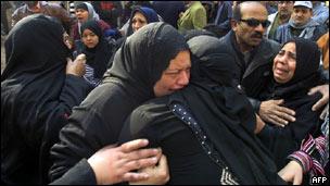 Mulheres choram em funeral de vítimas de confrontos em estádio