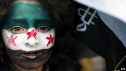 Niña participa en marcha en Londres con los colores de la primera bandera de la Siria independiente dibujados en el rostro