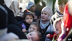 Sirios huyendo de Homs