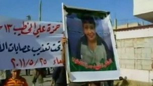 Militante carrega cartaz com rosto do jovem Hamza al Khatib, cujos parentes dizem ter sido morto por tropas sírias (BBC)