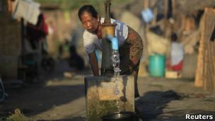 Mulher coleta água no Mianmar. | Foto: Reuters