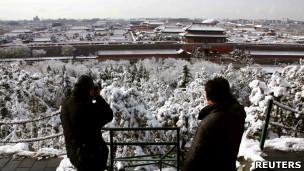 两名游人在北京景山公园的山岗上拍摄故宫(18/3/2012)