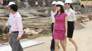 Tô Linh Hương, người mặc váy hồng, đi thăm công trường