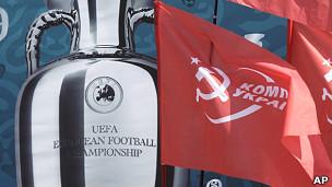 Флаги компартии Украины на фоне плаката Евро-2012