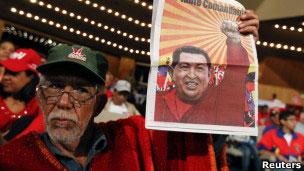 Simpatizante segura cartaz com imagem de Chávez
