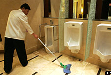 A Chinese worker cleans up a toilet