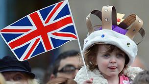 Chiquilla con corona y bandera
