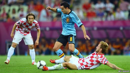 Pemain tengah Spanyol, Xavi, berebut bola dengan dua pemain Kroasia di Gdansk, Polandia.