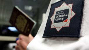 Funcionario fronterizo británico revisa pasaporte