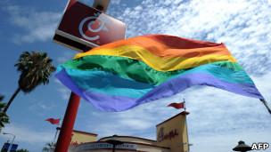 Bandera del movimiento gay ondea frente a un Chick-fil-A