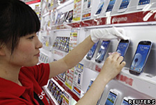 A shop assistant puts the Samsung Galaxy phone on display