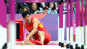 刘翔在起跑后准备跨越第一栏时摔倒