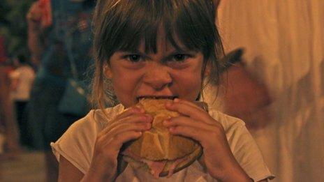 Niña comienod un sándwich