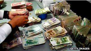 Un trabajador de un banco provincial en China cuenta billetes de yuan