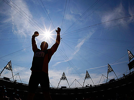 Australia's Russell Short stands silhouetted against the sun during the Men's shot put final at the Olympic Stadium.