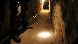 Un policia federal brilla una luz con su linterna en un tunel subterráneo en la frontera entre Mexico y EE.UU