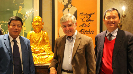 Ông Michael Dukakis (giữa), ông Nguyễn Anh Tuấn (bìa phải) cùng một người tham dự hội thảo Miến Điện chụp hình trước tượng Trần Nhân Tông.