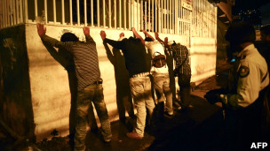 Policiais fazem revista de rotina em jovens em um dos bairros afetados pela violência em Caracas (AFP)
