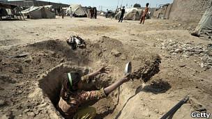 Niña paquistaní excavando un pozo