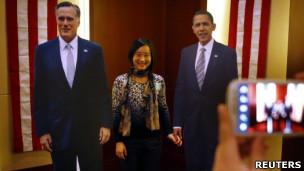 一名中国客人在美国驻北京大使馆主办的大选派对上与奥巴马和罗姆尼的纸板人像合照(7/11/2012)