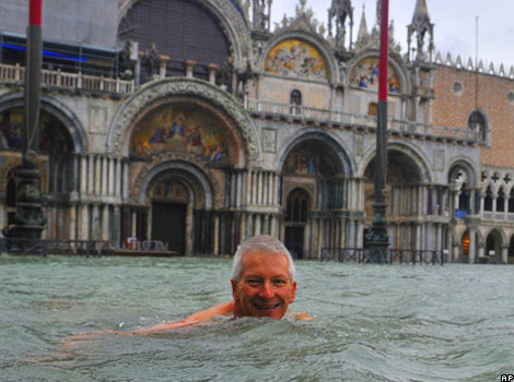 A man swims in Venice in a flooded St Mark's Square.