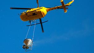 Helicóptero con un recipiente que transporta cebos letales para las ratas Foto: Martin Collins