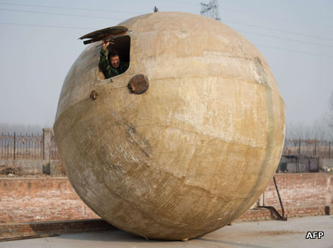 A Chinese farmer in a large ball called a 'survival pod'.