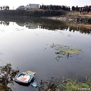 江西贵溪滨江镇校车坠塘事故现场一个书包在池塘上漂浮(新华社图片24/12/2012)