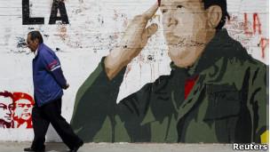 Venezuelano caminha em frente a mural com pintura em homenagem a Chávez (foto: Reuters)