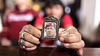Mujer sostiene un pequeño retrato de Chávez con sus manos.