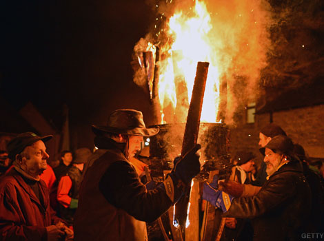 Men carrying a burning barrel