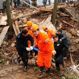 云南镇雄高坡村山体滑坡现场救援人员搬运一具遇难者遗体(11/1/2013)