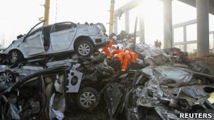 河南义昌大桥倒塌现场救援人员在一辆坠桥小轿车的残骸旁搜索(1/2/2013)