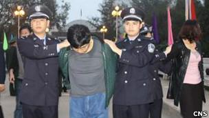 宋建国(中)被中国警察押回广西境内(中新社图片5/2/2013)