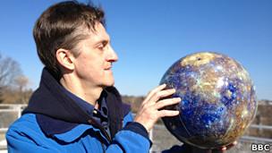 Американский ученый Дэвид Блюитт демонстрирует глобус Меркурия