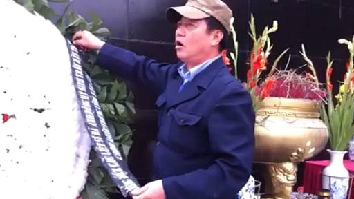 Một bảo vệ toan gỡ dòng chữ tưởng niệm những người ngã xuống trong cuộc chiến biên giới hôm 17/2/2013