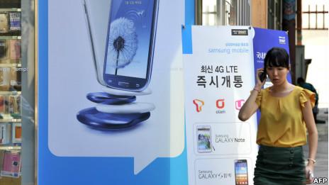 Mujer hablando frente a anuncio de Samsung, el gigante surcoreano que ya le pisa los talones a Apple