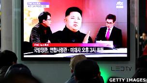 Transeúntes en Corea del Norte miran una tv con un debate sobre la crisis en la península