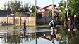 Moradores tentam atravessar área inundada na Argentina (BBC)