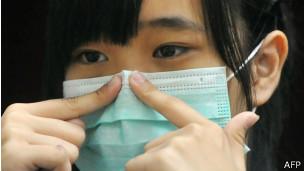 Jovem usa máscara na China, onde cem foram infectados pelo H7N9 (AFP)