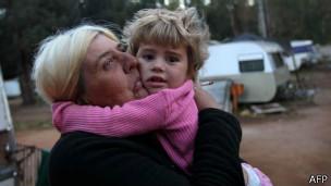 mulher com criança no colo (Foto: AFP)
