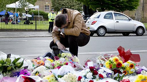 Hombre se lamenta frente a ramos de flores en Woolwich